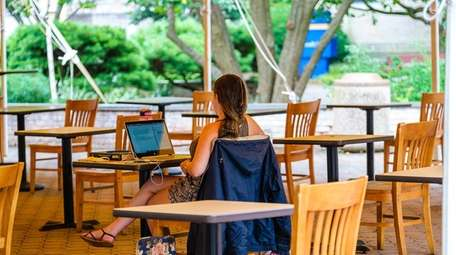 A student works outdoors this summer at Hofstra