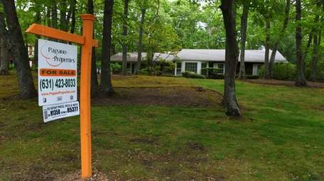 A for-sale sign on a Dix Hills property