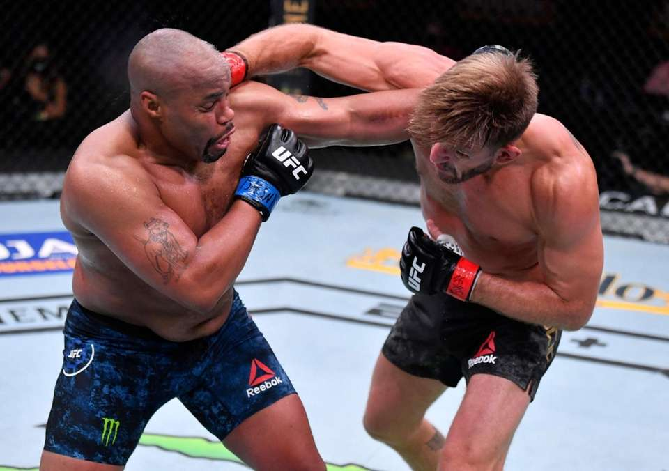 Stipe Miocic (R) punches Daniel Cormier in their