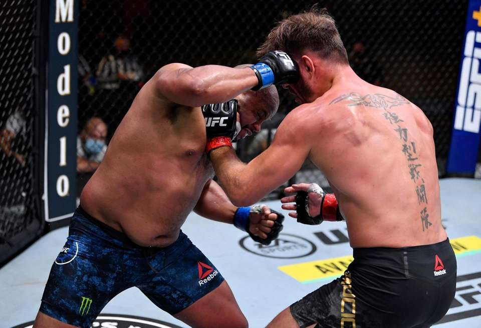 Daniel Cormier (L) punches Stipe Miocic in their
