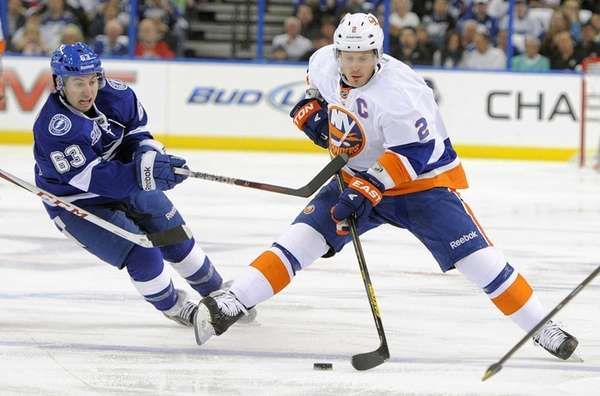 Islanders defenseman Mark Streit battles for the puck