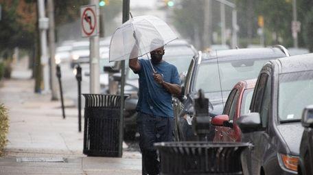 A man with an umbrella walks along Merrick
