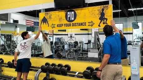 Power 10 Gym owner Steve Panzik, right, smooths