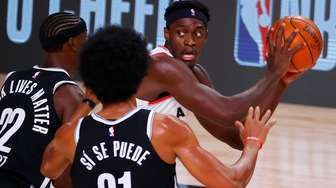 Toronto Raptors' Pascal Siakam, right, is trapped by