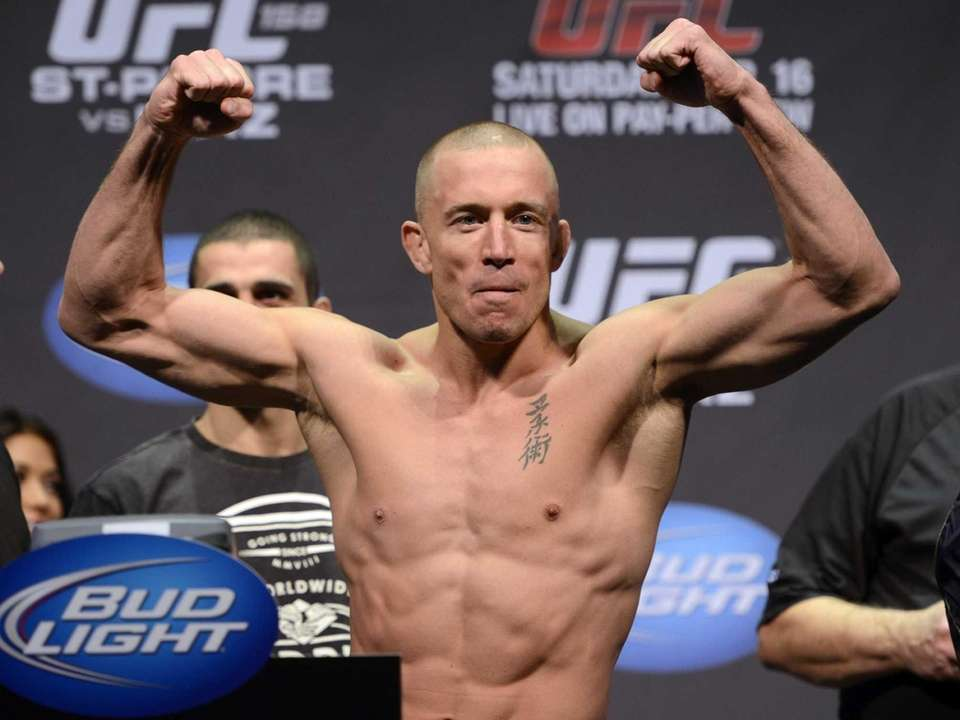 Fighter Georges St-Pierre flexes during the weight-in for