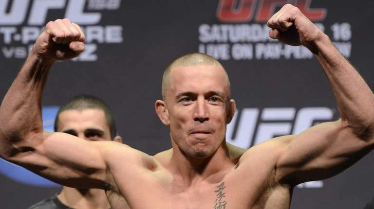 Fighter Georges St-Pierre flexes during the weigh-in for