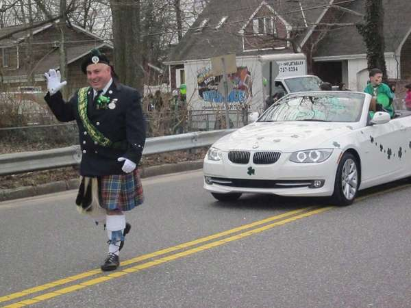 Parade grand marshal Thomas Donohue waves to the