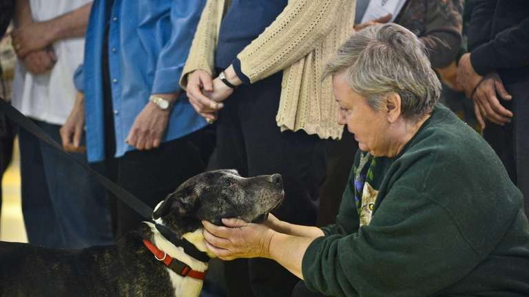 Jane Totura, of Greak Neck, pets a mix