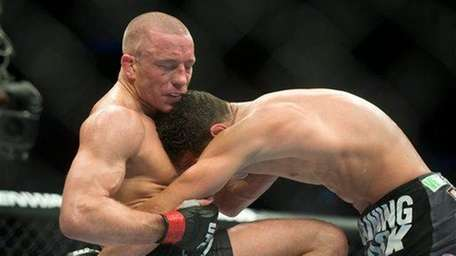 Georges St-Pierre, left, lands a knee to the