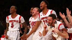 Louisville Cardinals players celebrate on the bench during