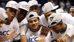 Shane Larkin, center, of the Miami holds the