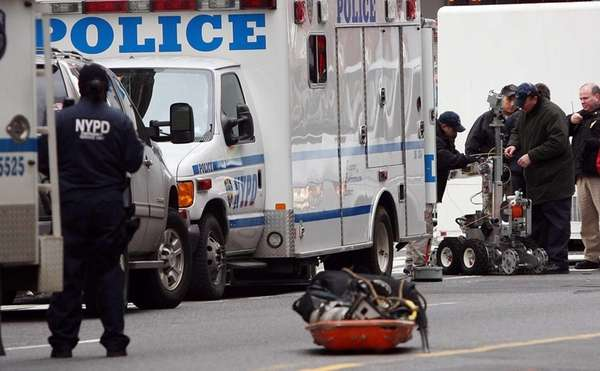 Police bomb squad members prepare a robotic camera