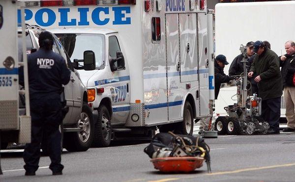 Police bomb squad members prepare a robotic camera
