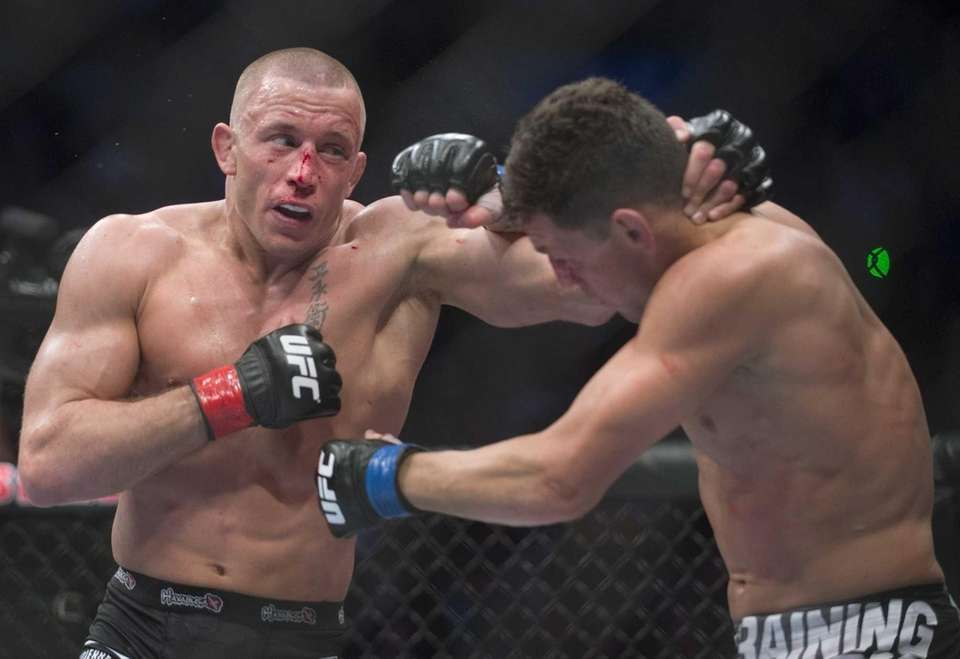 Georges St-Pierre, left, lands a blow to Nick
