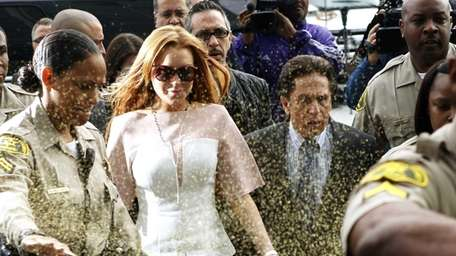 Lindsay Lohan is showered with gold glitter as
