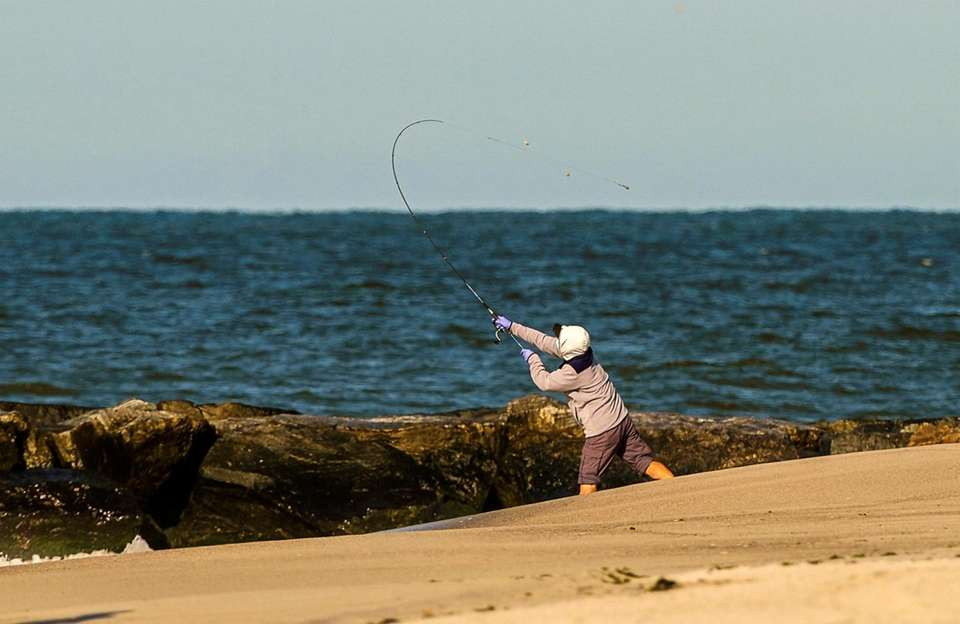 A fisherman casts his line into the surf
