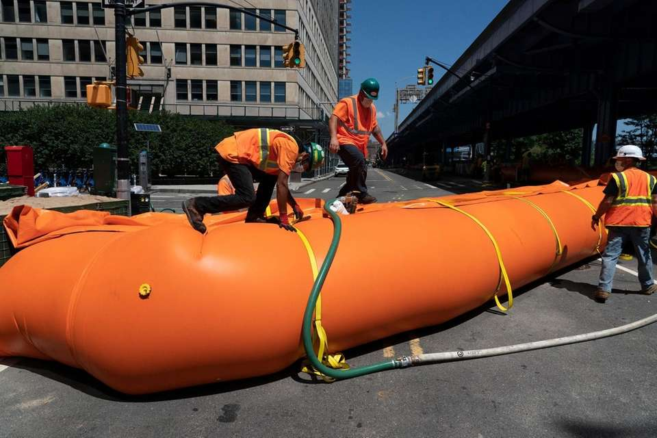 Contractors install temporary flood barriers along South Street