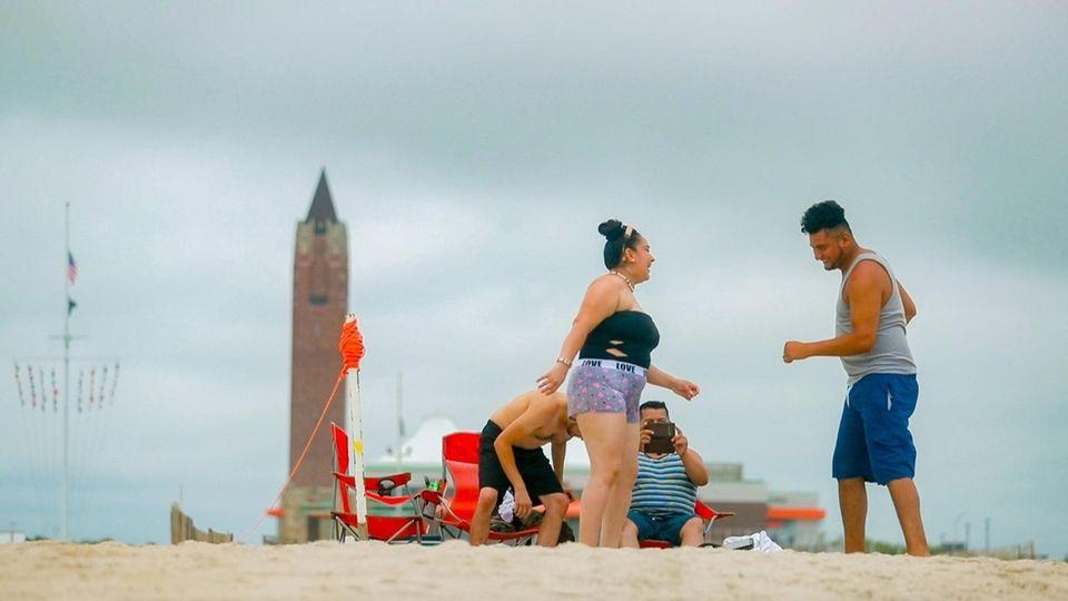 Beach go-ers enjoy an overcast day ahead of