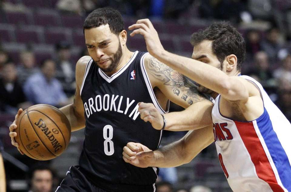 Deron Williams (8) is tightly guarded by Detroit