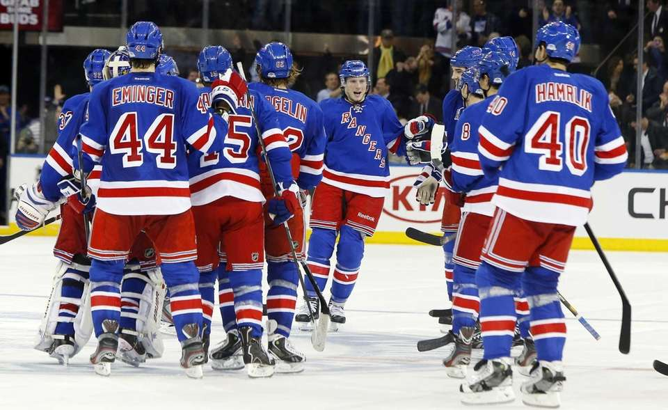 J.T. Miller, center, celebrates his game-winning shootout goal