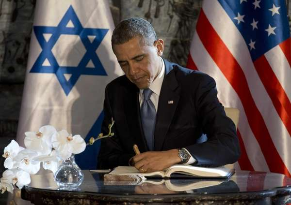 President Barack Obama signs a guest book at
