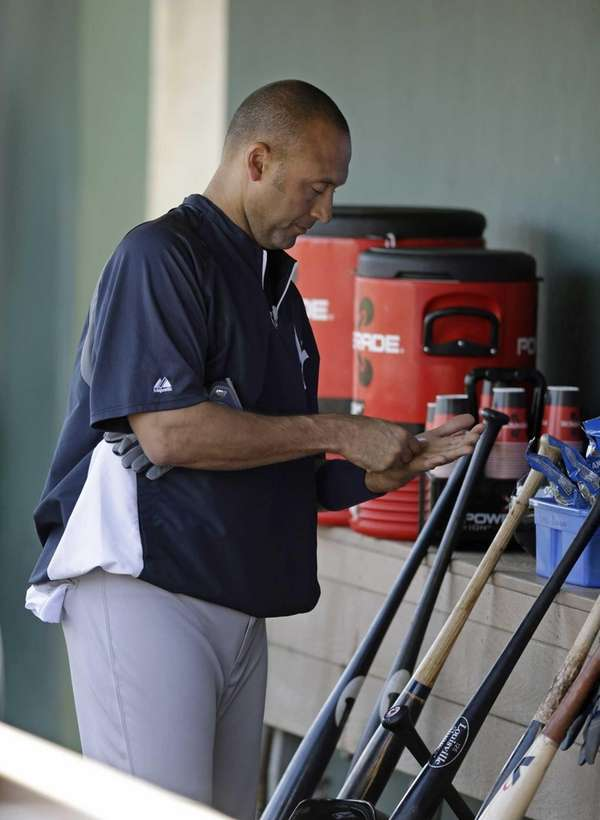 Derek Jeter prepares in the dugout before taking