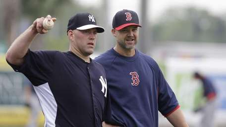 Yankees third baseman Kevin Youkilis, left, throws a