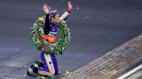 Takuma Sato of Japan celebrates after kissing the