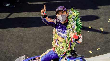 Takuma Sato of Japan celebrates after winning the
