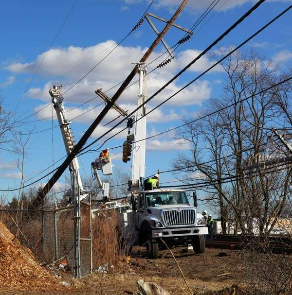 LIPA crews work on a pole leaning over