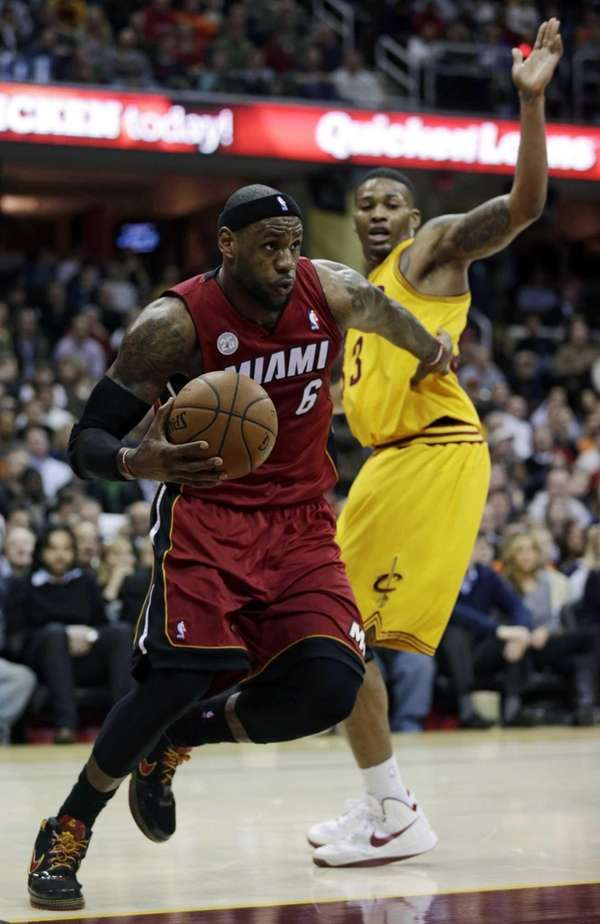 Miami Heat's LeBron James drives past Cleveland Cavaliers'