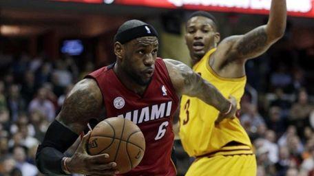 Miami Heat's LeBron James drives past Cleveland Cavaliers'
