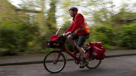 A Royal Mail Group Ltd. employee rides his