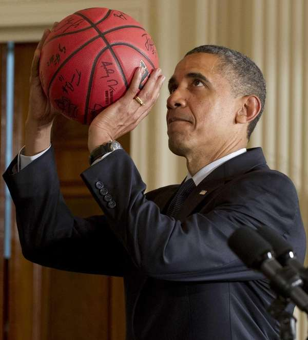 President Barack Obama pretends to shoot a basketball
