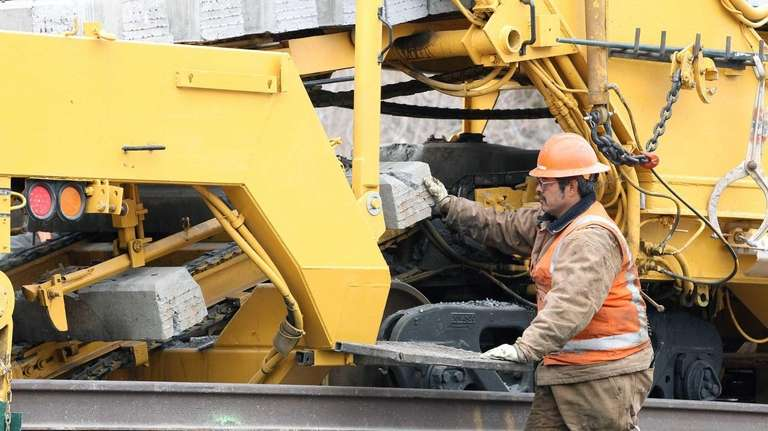 LIRR track maintenance personnel use heavy machinery to
