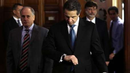 Gov. Andrew Cuomo checks his watch as he