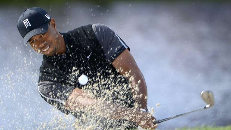 Tiger Woods hits out of a bunker onto