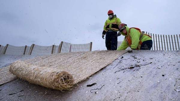 A worker stabilizes the dunes to protect the