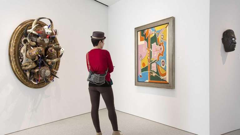 A visitor pauses at a painting on view
