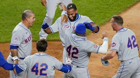 The Mets' Amed Rosario , center, runs home