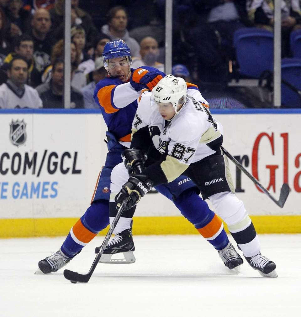 Travis Hamonic of the Islanders defends against Sidney