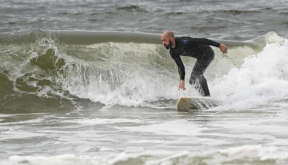 A surfer at Smith Point County Beach in