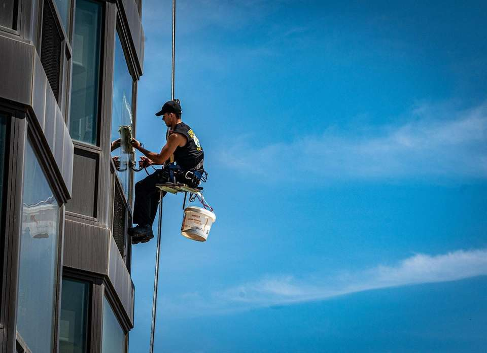 Hanging from a harness a man cleaning the