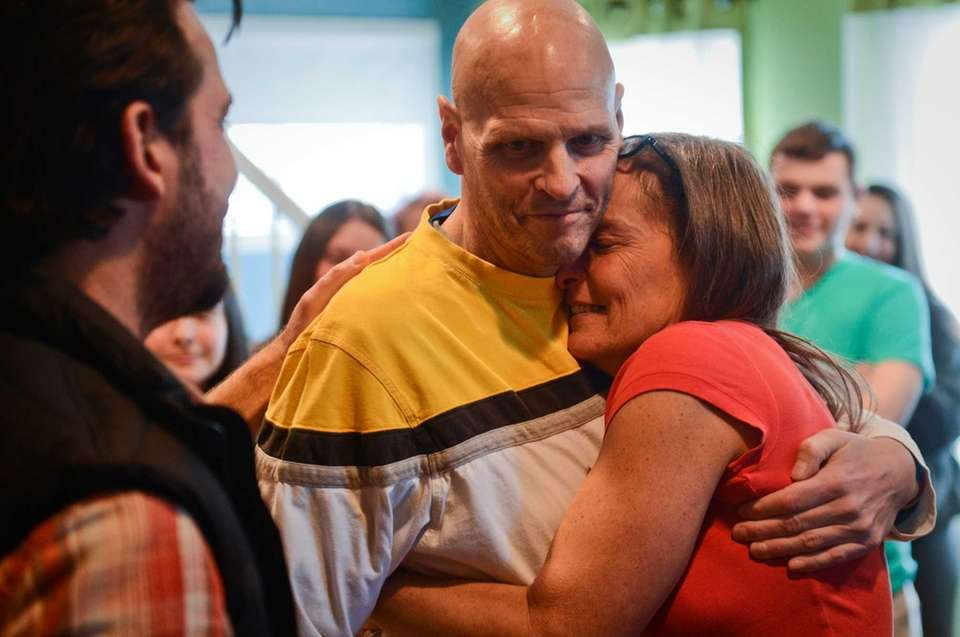 Lori Enright hugs her husband, John, after viewing