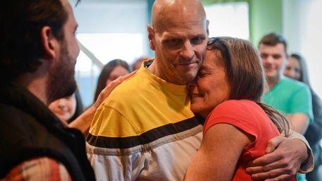Lori Enright hugs her husband, John, after viewing