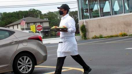 A server carries food Monday through the parking