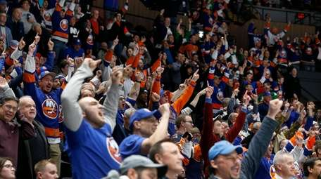 Islanders fans cheer a third-period goal against the