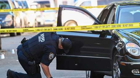An NYPD emergency service officer examines a bullet