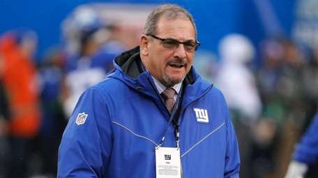 Giants general manager Dave Gettleman watches warm ups