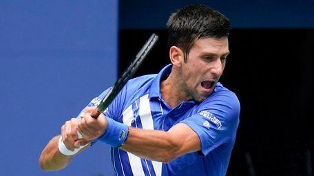 Novak Djokovic returns a shot to Kyle Edmund